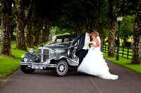 Just married couple sharing a kiss by vintage car